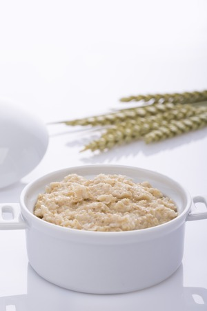 Oatmeal and bran in a white pot. Healthy food.
