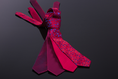 windsor: silk ties in different colors, spread out on a black tabl