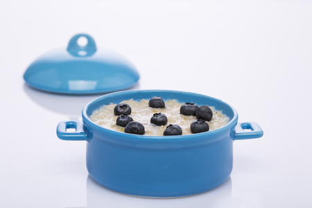 Oatmeal and blueberries in blue pan. Healthy food.