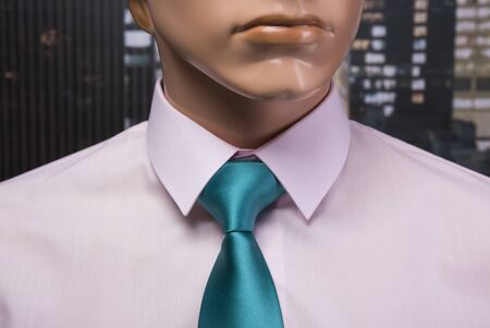 Pink shirt and green tie placed on a mannequin