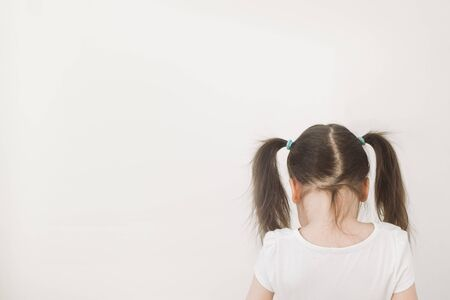 A girl with two ponytails stands with her back to the camera. The child turned away to the light wall. Upset baby crying