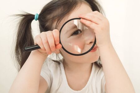 Little girl plays a detective. A child examines something through a magnifying glass. A girl with two ponytails plays cute. Toddler indulges with a magnifier Stock fotó