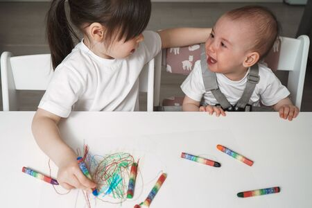 Sisters draw with crayons. The little sister cries very much. Quarrel between children at home. Older children conflict with younger ones