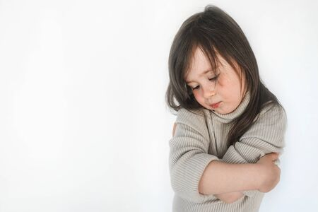 Sad child hugs himself. Place for advertising. Little girl hugs herself and is afraid.