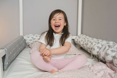 Joyful child getting ready for bed. The baby is sitting on the bed and rejoices