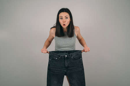 The girl lost a lot of weight. The girl is holding very large jeans. The woman is surprised how she lost weight. Problems of female anorexia