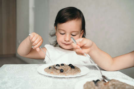 A small child eats oatmeal with berries. The girl holds a spoon in her hands. The sisters have breakfast at the table. Oatmeal in a white flat plate. Morning porridge with blueberries. Stock Photo