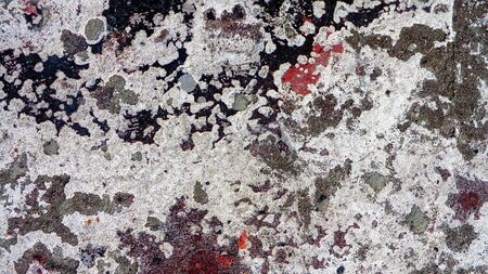 dirty stone wall texture with stains of black, gray and red shabby paint