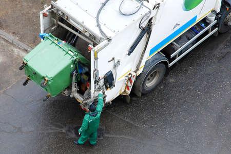 Garbage man operating garbage truck in residential area, everyday garbage removal