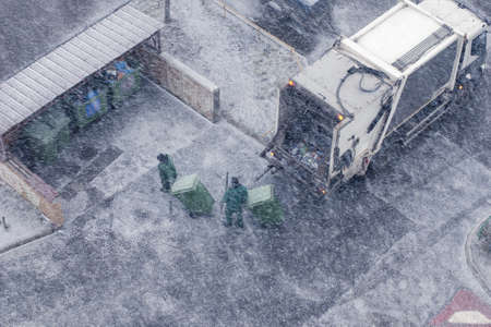 Garbage truck and two workers in snow storm, top view