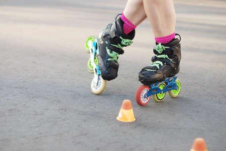roller skater legs in motion, inline roller skating, rollerblading, slalom on asphalt surface. Small cones for training on the road.