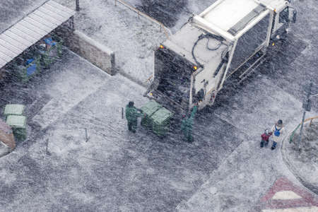 Garbage men in snow storm working in residential area Banque d'images