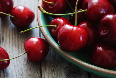 cherries in a bowl on wooden table closeup