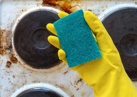 hand in yellow glove holding washup sponge against dirty electric stove