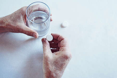 Elderly man hands taking medicine pill with a glass of water Stock fotó - 154833717