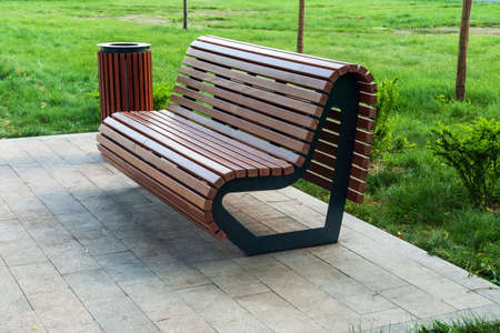 modern park bench and waste bin made of wooden planks