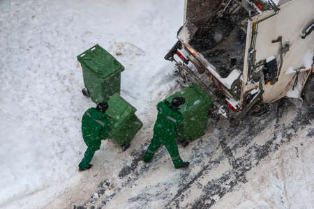 garbage collection workers pick up household waste in winter