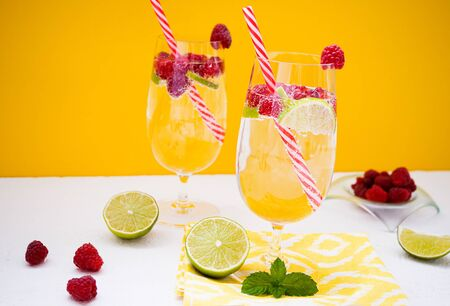 A refreshing drink with lime and raspberries in beautiful glasses stands on a white table against the background of an yellow wall. On the table are slices of lime, raspberries and a bowl with berry. Stock fotó