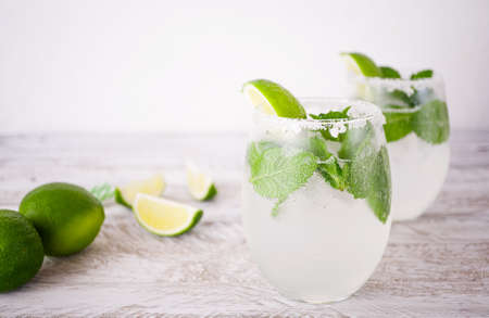 A refreshing drink with lime and mint in transparent glasses stands on a wooden table against the background of a white wall. Near by lie slices of juicy lime and striped cocktail tubes.