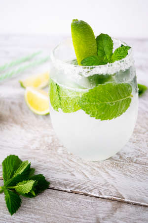 One glass of refreshing drink with lime and mint stands on a light wooden table. Near are fresh mint leaves. The edges of the glass are grated with lime and coated with salt. Vertically Imagens