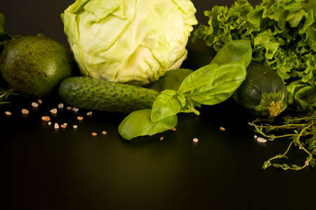 Healthy eating vegan produce. Green vegetables and fruits on dark background: cabbage, avocado, zucchini, cucumbers, basil, thyme, lettuce salad.
