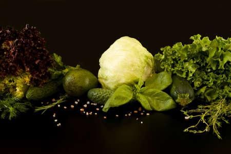 Fresh green food selection, green fresh salad and lollo salad, cucumber, ripe avocado, cabbage, basil, thyme, zucchini, rose salt. Set raw green vegetables on a dark background, close-up. Reklamní fotografie