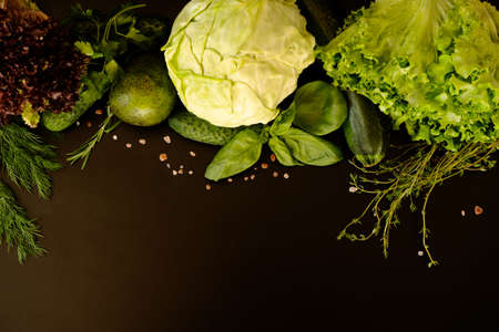 Flat lay fresh vegetables and herbs on a dark background with a place for text. Young green salad, thyme, basil, cabbage, cucumber, avocado, zucchini, dill, parsley. Reklamní fotografie