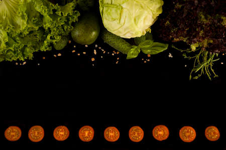 Healthy food: green salad, lollo salad, thyme, basil, cabbage, cucumbers, avocado. Red tomato slices arranged in a line against a dark background; top down view of tomatoes arranged as a boarder. Reklamní fotografie
