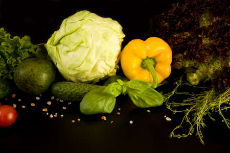 Vegetarian food. Yellow sweet bell pepper, cherry tomato and green vegetables on dark background, close-up.