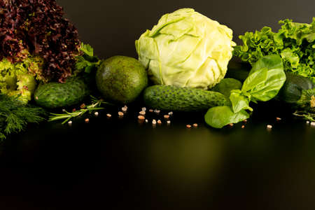 Vegan diet food background: salad, cucumber, avocado, cabbage, basil, thyme, zucchini. Healthy lifestyle concept. Set raw green vegetables on the dark surface, close-up.
