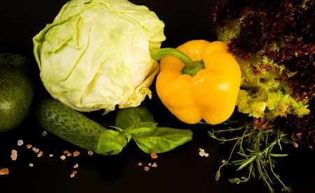 Vegetable dietetic fresh food. Yellow sweet bell pepper, cole, green salad, ripe avocado, big leaves basil, rose salt on dark background, close-up.