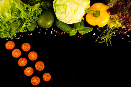 Fresh vegetables: yellow pepper, green salad, cole, ripe avocado, rose salt are lined at the top on a dark background. Juicy tomato slices lay for two diagonal line. Reklamní fotografie - 150620645