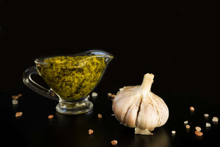 Italian sauce pesto in glass sauceboat isolated and garlic head, with rose salt on black background.