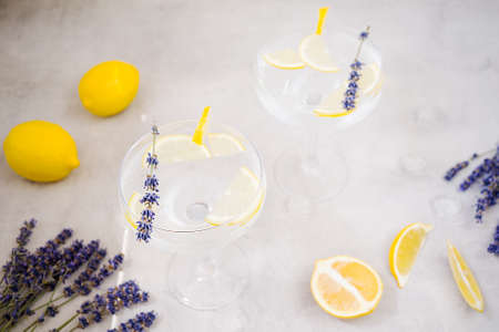 Refreshing infused water with lemon in beautiful glasses stands on a gray stone background. Glasses are decorated with a slice of lemon and lavender. Near are lemons. Detox morning drink, clean food. 版權商用圖片