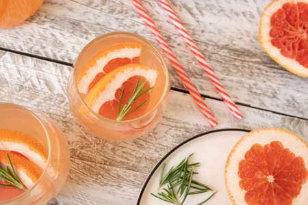 A glass of infused water with grapefruit slices and rosemary stands on a light wooden table. Nearby lie hollow cocktail tubes and there is a white bowl with chopped grapefruit. Top view, close up