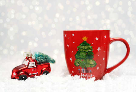 A large red mug stands on the white snow. Nearby lies a Christmas decoration, a red car with a Christmas tree. Bokeh in the background. Christmas and New Year concept. Close-up