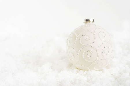 Christmas background with decoration for the tree. White glass ball with patterns lies on white snow. Free space for text on the left. Close-up