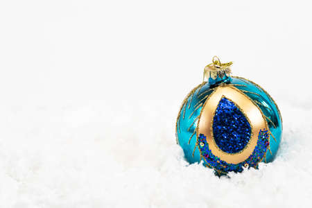One shiny glass ball (blue, gold) for the Christmas tree lies on white snow. Christmas decoration on a white background. Bokeh in the background. Close-up