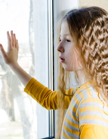 the sad child looks out of the window photo