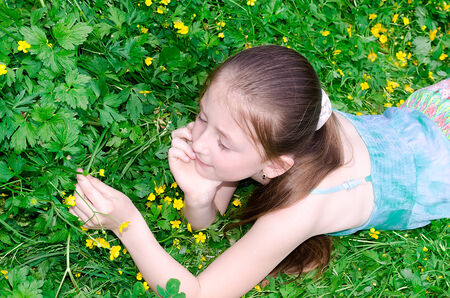 the child has a rest on a glade with flowers photo