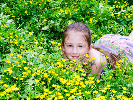 the child the girl has a rest on a glade with flowers photo