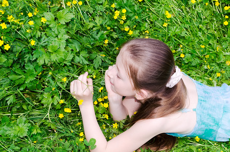 the child the girl lies on a glade with flowers photo
