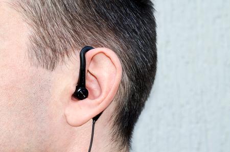 the earphone in an ear of the man photo