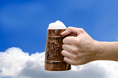 beer glass in a hand against the sky photo