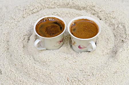 two cups with coffee stand on sand photo