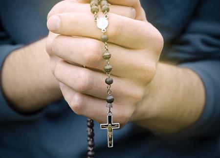 orando: hombre reza con un rosario en las manos
