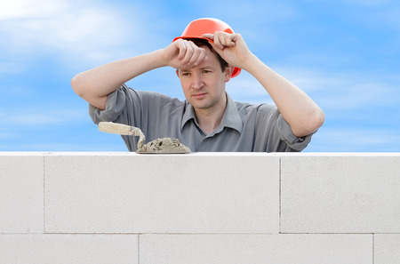 Construction worker wiping the sweat from his forehead photo