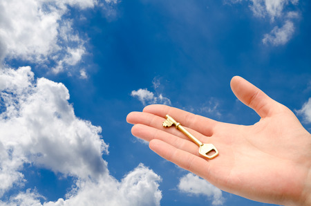 homebuyer: hand with a key in the sky