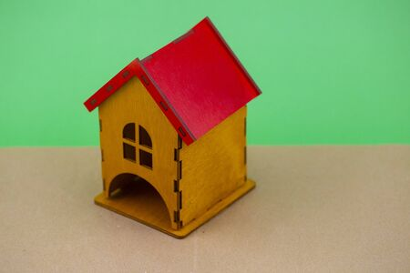 wooden house with a red roof on a green background.conceptual photo