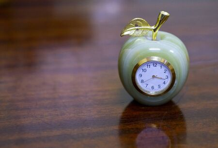 retro clock in the shape of an Apple on the polished table Stock Photo